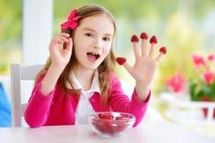 Nätt liten flicka som hemma äter hallon Gulligt barn som tycker om hennes sunda nya frukter och bär Fotografering för Bildbyråer