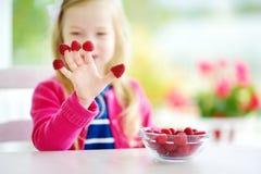 Nätt liten flicka som hemma äter hallon Gulligt barn som tycker om hennes sunda nya frukter och bär Arkivfoto
