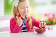 Nätt liten flicka som hemma äter hallon Gulligt barn som tycker om hennes sunda organiska frukter och bär Arkivfoto