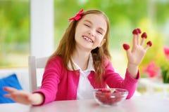 Nätt liten flicka som hemma äter hallon Gulligt barn som tycker om hennes sunda organiska frukter och bär Royaltyfria Bilder