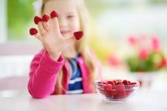 Nätt liten flicka som hemma äter hallon Gulligt barn som tycker om hennes sunda organiska frukter och bär Arkivbild
