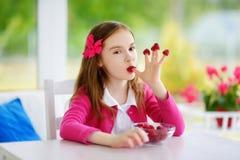 Nätt liten flicka som hemma äter hallon Gulligt barn som tycker om hennes sunda organiska frukter och bär Fotografering för Bildbyråer