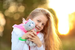 Nätt liten flicka som kramar ett favorit- välfyllt djur - en katt för royaltyfri fotografi