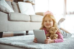 Nätt liten flicka som ligger på golv med den moderna apparaten royaltyfri bild