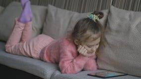 Nätt liten flicka som ligger på soffan genom att använda minnestavlan Småbarn som hemma spelar på bärbara datorn på en orange sof lager videofilmer