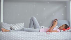 Nätt liten flicka som lyssnar till musik i hennes säng stock video