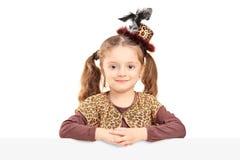 Nätt liten flicka som poserar bak den vita panelen Royaltyfria Bilder