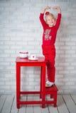 Nätt liten flicka som poserar nära tabellen Royaltyfri Bild