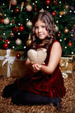 Nätt liten flicka som rymmer en julprydnad Arkivbild