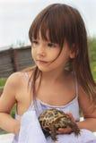 Nätt liten flicka som rymmer en rysssköldpadda Fotografering för Bildbyråer