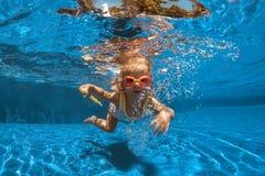 Nätt liten flicka som simmar i simbassäng royaltyfri foto