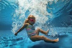 Nätt liten flicka som simmar i simbassäng arkivfoton