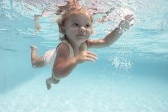 Nätt liten flicka som simmar i simbassäng fotografering för bildbyråer