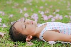 Nätt liten flicka som sover på grönt gräs med den rosa blomman för nedgång i den utomhus- trädgården royaltyfri foto