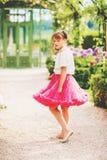 Nätt liten flicka som spelar i en härlig trädgård Arkivbilder