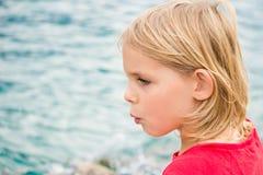 Nätt liten flicka som visslar vid sjön royaltyfri bild