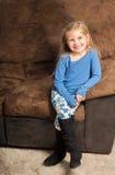 Nätt liten flickasammanträde på en soffa med ett stort leende Royaltyfri Fotografi