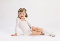 Nätt liten flickasammanträde på golvet och göraövningen royaltyfria foton