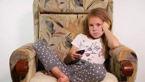 Nätt liten flickasammanträde på soffastol och ändrande kanaler med fjärrkontroll lager videofilmer