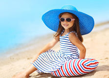Nätt liten le flicka i en randig klänning- och sugrörhatt som kopplar av att vila på stranden nära havet Arkivbild