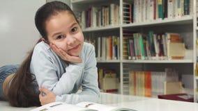 Nätt liten lycklig asiatisk flicka som ler enjoyign som läser en bok fotografering för bildbyråer