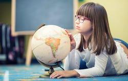 Nätt liten studentflicka som studerar geografi med jordklotet i barns rum royaltyfri foto