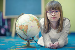 Nätt liten studentflicka som studerar geografi med jordklotet i barns rum royaltyfria bilder