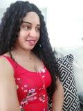 Nätt lockig kvinna för svart hår i röd sikt för blommaklänningsida royaltyfri foto