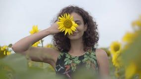 Nätt lockigt skämtsamt le flickaanseende på solrosfältet Ljus gul f?rg svart isolerad begreppsfrihet lycklig kvinna stock video