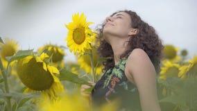 Nätt lockigt skämtsamt le flickaanseende på solrosfältet Ljus gul f?rg svart isolerad begreppsfrihet lycklig kvinna arkivfilmer