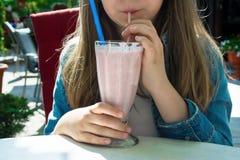 Nätt lycklig flicka som dricker jordgubbesmoothien Royaltyfri Bild