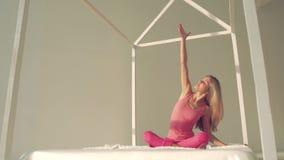 Nätt mässa-flådd yogakvinna som gör yoga i säng stock video