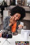 Nätt mörkhyad kvinna med korallläppstift som gör makeup royaltyfria foton