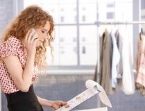 Nätt modeformgivare i arbete genom att använda mobiltelefonen Arkivfoton