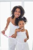 Nätt moder med hennes dotter som borstar deras tänder Arkivbilder