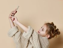Nätt modern flicka i enorm tröja som ler och gör selfie på smartphonen fotografering för bildbyråer