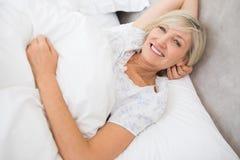 Nätt mogen kvinna som vilar i säng Arkivbild