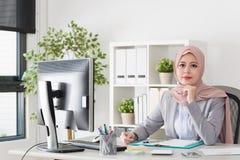 Nätt muslimaffärskvinna som i regeringsställning arbetar royaltyfria bilder