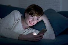 Nätt och lycklig röd hårkvinna på hennes 20-tal eller 30-tal som ligger på den hem- soffan eller säng genom att använda mobiltele Arkivbilder