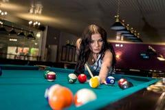 Nätt och ung kvinna som spelar billiard i bar royaltyfria bilder