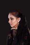 Nätt orientalisk kvinna i abaya på svart bakgrund Fotografering för Bildbyråer