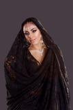 Nätt orientalisk kvinna i abaya på svart bakgrund Arkivbild