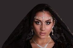 Nätt orientalisk kvinna i abaya på svart bakgrund Arkivbilder