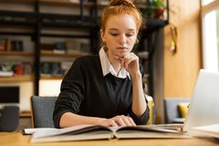 Nätt röd haired tonårs- flicka som använder bärbar datordatoren royaltyfria foton