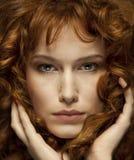 Nätt rödhårig flicka med krullning, fräknar, stående royaltyfria foton