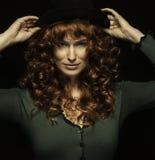 Nätt rödhårig flicka med krullning med frackles, svart hatt Fotografering för Bildbyråer