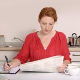 Nätt rödhårig kvinna som söker för jobb royaltyfri fotografi