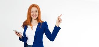 Nätt rödhårig manflicka med telefonen som ler peka fingerrätt på vit bakgrund Den unga rävaktiga kvinnlign i affärsdräkt, arkivfoton