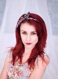 Nätt rödhårig mankvinna i en blom- klänning Arkivfoto