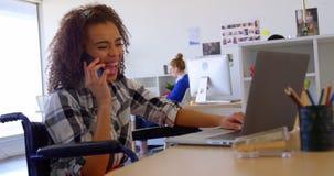 Nätt rörelsehindrat blandad-lopp kvinnlig ledare som talar på mobiltelefonen, medan genom att använda av bärbara datorn i modernt lager videofilmer
